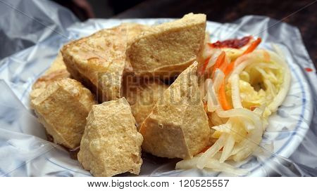 Fried stinky tofu with pickle vegetable and sauce on the side. Serve on plastic over plate ** Note: Shallow depth of field