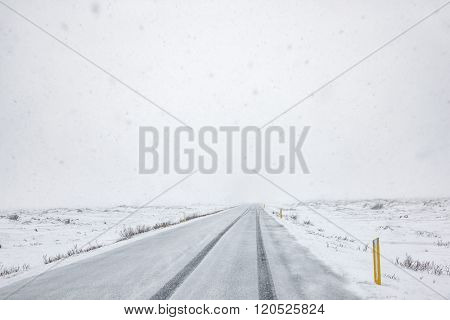Snow falling on a country road in iceland in the winter