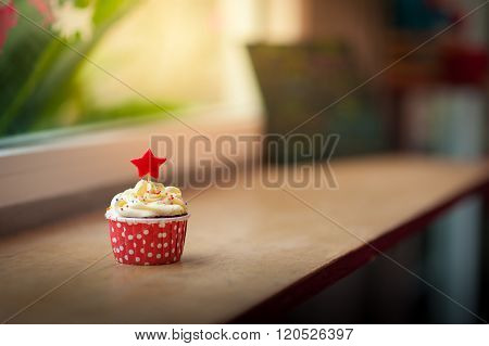 Small red velvet cupcake with cream that made from yogurt and cream cheese garnished with star shape fondant and colourful sugar sprinkle on wood bar in cafe in morning time with low key scene