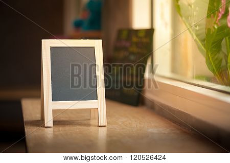 Small A-frame black board with blank area for text or message on wood bar in cafe wih low key scene