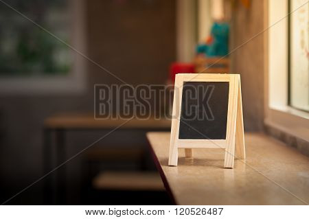 Small A-frame black board with blank area for text or message on wood bar in cafe at morning time