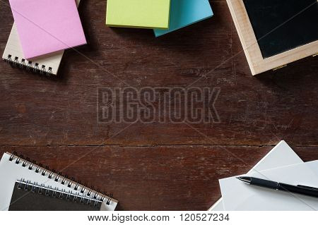 Notebooks small black board blank paper sticky paper on wood table with low key scene