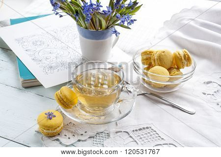 A cup of hot tea, flowers blue snowdrop, sketchbook and lemon macaroons on a light background