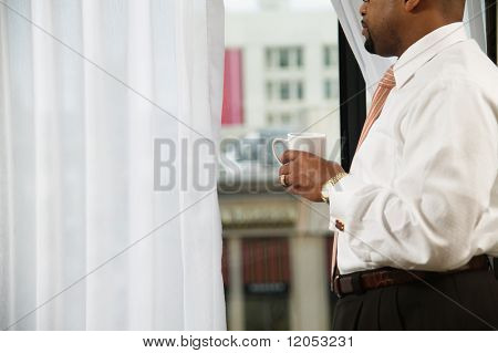 Midsection of businessman looking out window