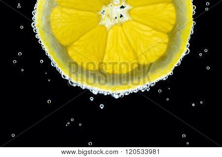 Slice of lemon in the gas water on the black