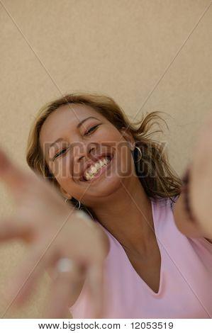 Portrait of young woman reaching toward camera