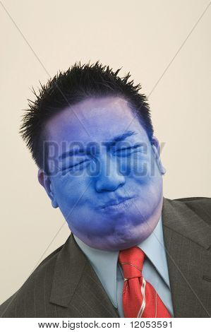 Young businessman holding breath and turning blue
