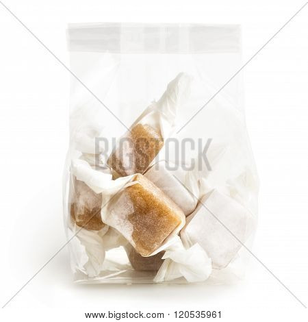 Isolated Cellophane Packet Of Wrapped Caramel Toffees.