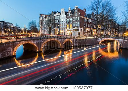 A view of the bridges at the Leidsegracht and Keizersgracht canals intersection in Amsterdam at dusk. The trail from a boat can be seen.