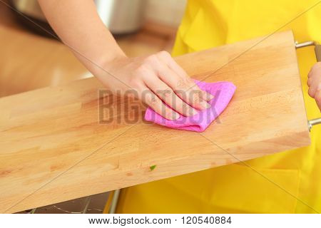 Woman Cleaning Wooden Cutting Board With Rag