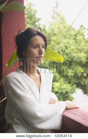 Woman in spa robe leaning on railing