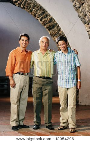 Three generations of men posing for the camera