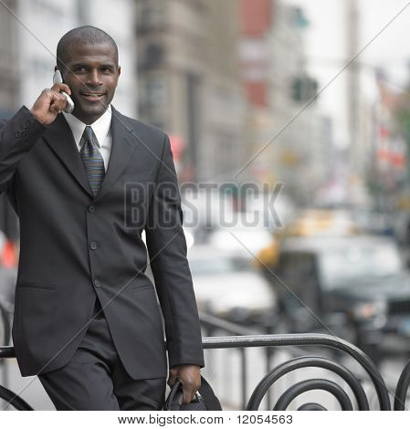 Businessman walking while talking on cell phone