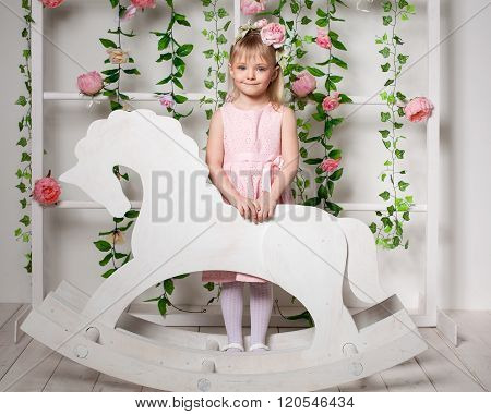 Portrait Of A Little Blonde Girl  Standing Near The Wooden Horse Rocker