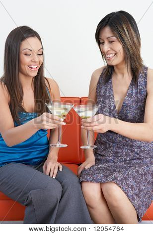 Young women toasting each other with martinis