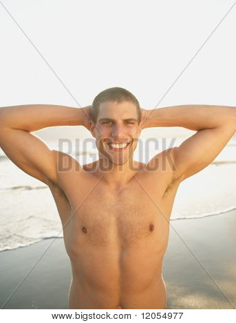 Portrait of man without shirt smiling with hands behind head