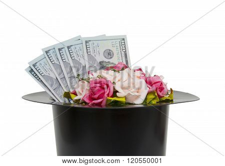Money and flowers in black magic hat isolated on a white backgroundm