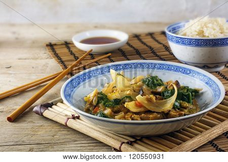 Asian Vegetable Dish With  Rice And Soy Sauce On A Bamboo Mat And A Rustic Wooden Table