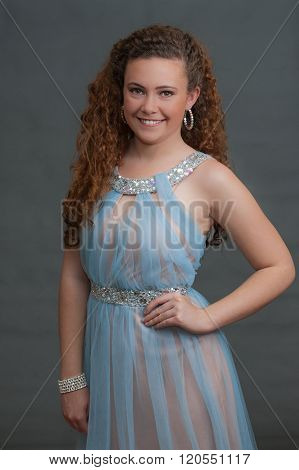 Teen beauty in blue dress smiling forward.
