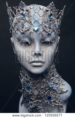 Mannequin in creative silver snow queen crown and collar on dark background