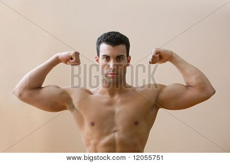 Portrait of man without shirt flexing biceps