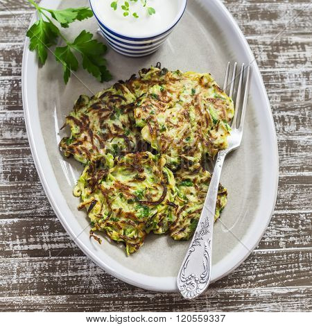 Zucchini Fritters With Herbs On A Ceramic Plate On A  Wooden Background. Healthy, Vegetarian Food