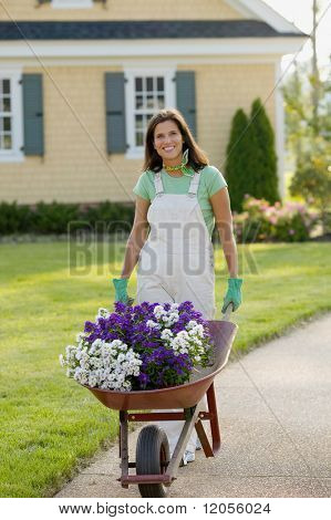 Portrait of woman with wheelbarrow full of flowers