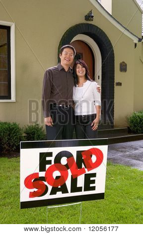 Couple standing outside their new home