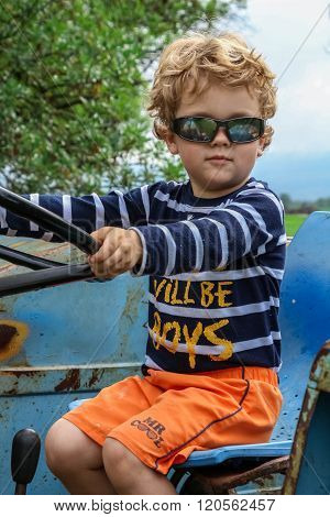 Cool Blonde 3 Year Old On A Blue Tractor