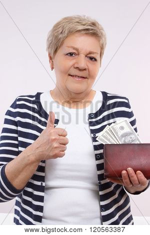 Senior Woman Holding Wallet With Currencies Dollar And Showing Thumbs Up, Concept Of Financial Secur