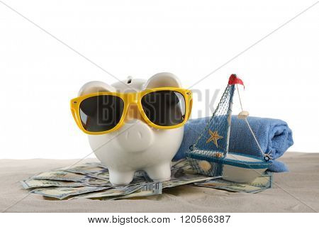 Piggy bank with dollar banknotes, towel and sunglasses on a sand, isolated on white. Holiday money concept