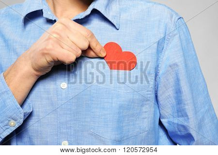 Young man hiding red heart in pocket shirt, close up