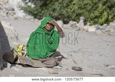 LEH INDIA - SEPTEMBER 08 2014: Unknown poor woman begs for money from a passerby on the street in Leh Ladakh. Poverty is a major issue in India