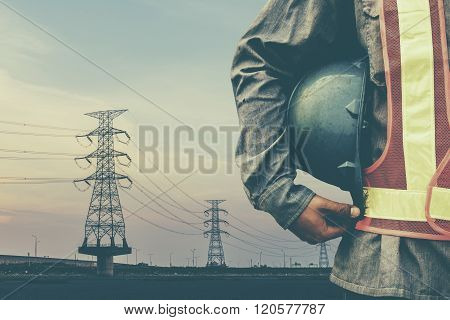 engineer holding blue helmet standing on silhouette high voltage post.High-voltage tower sky backgro
