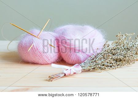 Two Skeins Of Pink Yarn With Knitting Needles On A Wooden Background With A Beam Of Near Artemisia