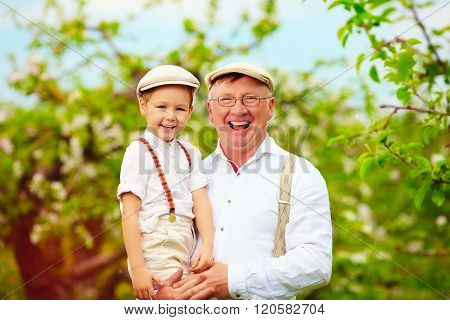 Joyful Grandpa And Grandson Having Fun In Spring Apple Garden