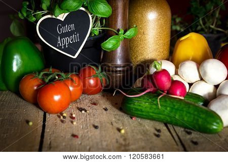 A Lots Of Healthy Vegetables On A Wooden Table, Heart With Text Guten Appetit
