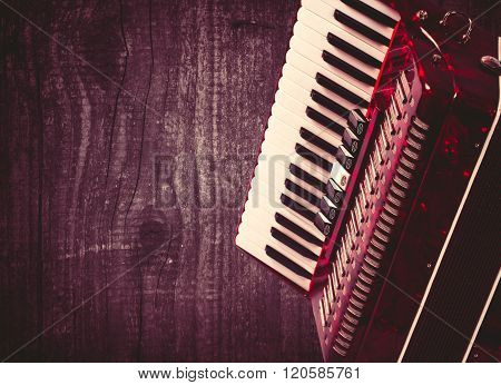 Part red accordion on wooden grey background. Write text. Vintage