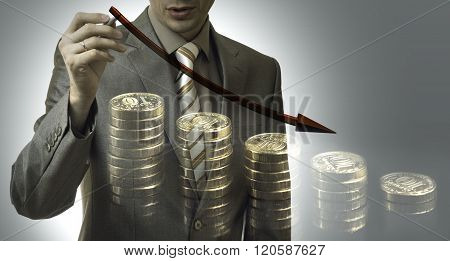 Business Concept. Businessman Drawing A Graph Down With Coins