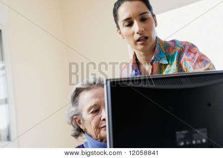 Elderly woman learning to use a computer