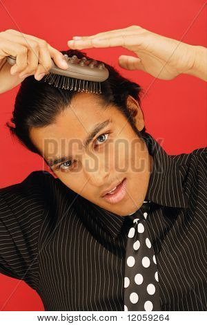 Portrait of businessman combing hair