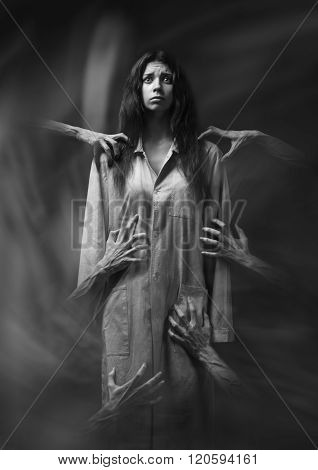 girl in a dirty robe hand of death nightmares insomnia a mentally ill woman halloween theme creepy dream hands of the demon hands of the devil in the smoke horror movie scene with a girlfear in studio black and white