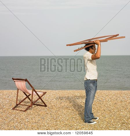Young man with lounge chair above his head at beach