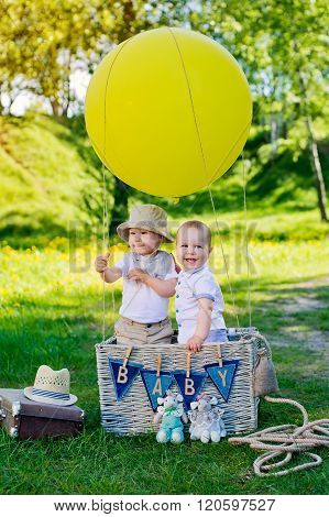 little boy in a basket with  balloon