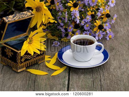 Casket, Coffee And Bouquet Of Flowers