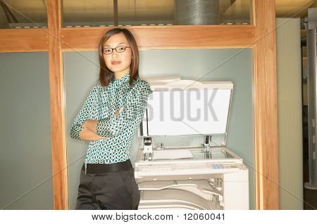 Businesswoman leaning on copy machine
