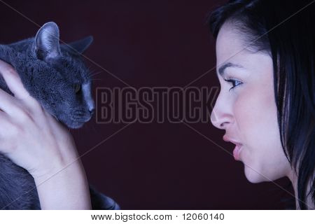 Young woman talking to her cat