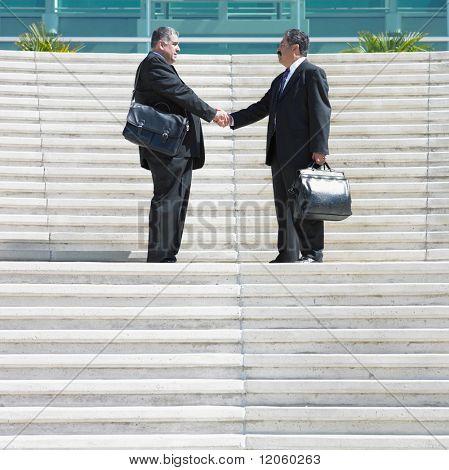Two businessmen shaking hands on steps