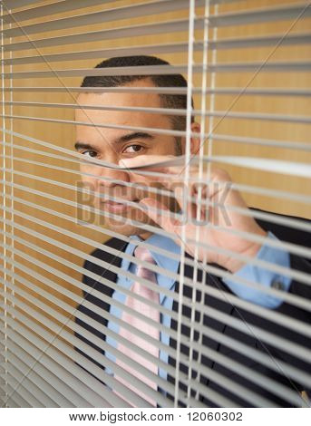 Businessman peering through blinds