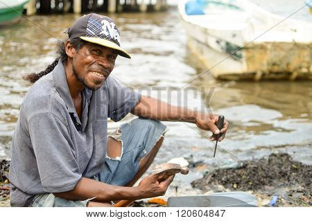 Creole man repairing his boat, Pearl lagoon, Nicaragua